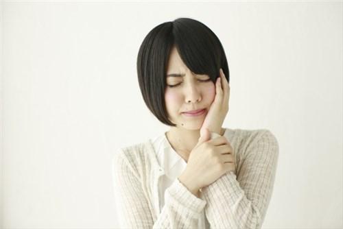 突然の歯痛に悩む女性